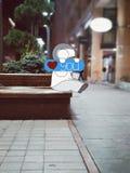 Personnage de dessin animé se reposant sur un banc en Arménie, Erevan tenant le beau signe photographie stock libre de droits