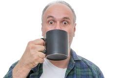 Personne étonnée avec la tasse devant le visage Image stock