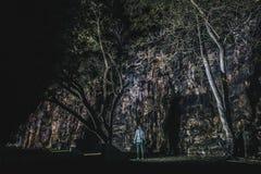 Personne anonyme près de caverne et d'arbres photo libre de droits