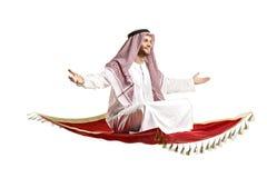Personne arabe s'asseyant sur un tapis de vol Photographie stock libre de droits
