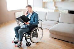 Personne avec les besoins sp?ciaux dans le fauteuil roulant Jeune ?tudiant regardant le livre ouvert et parlant au t?l?phone Seul photo libre de droits