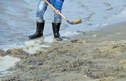 Personne dans des bottes en caoutchouc sur la plage Photos libres de droits