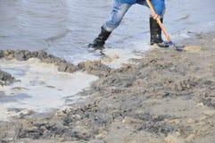 Personne dans des bottes en caoutchouc sur la plage Photo stock