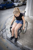 Personne dans le fauteuil roulant essayant de traverser la route Images stock