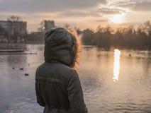 Personne dans le manteau chaud épais par l'étang en hiver Photographie stock libre de droits