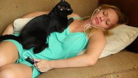 Personne dormant pendant le jour sur le divan avec des écouteurs du téléphone 4K Le mouvement lent, le chat noir se trouve sur banque de vidéos