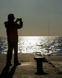 Personne en silhouette sur la pêche de pilier Photographie stock libre de droits