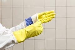 Personne enlevant des gants pour le travail, la précaution et l'hygiène Photo libre de droits
