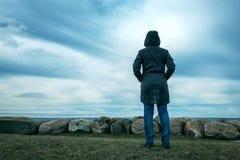 Personne féminine à capuchon seule par derrière la position au bord de la mer photos stock