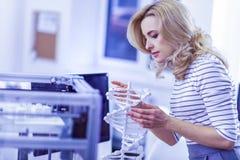Personne féminine attentive examinant le modèle à chaînes moléculaire image stock