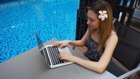 Personne féminine avec le message de dactylographie de fond bleu de piscine par l'ordinateur portable banque de vidéos