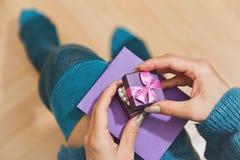 Personne féminine dans les bas déballant le cadeau Photo stock