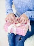 Personne féminine de plan rapproché gardant le cadeau sur des genoux photographie stock libre de droits