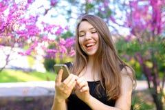 Personne féminine de sourire à l'aide du smartphone dans le parc avec le fond de fleur Photos libres de droits