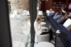 Personne féminine employant le filet-livre pendant le petit déjeuner de matin dans le café moderne photo libre de droits