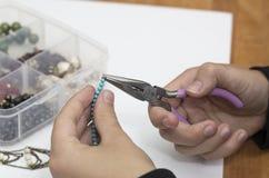 Personne faisant des bijoux avec des perles et d'autres matériaux avec des outils Photo stock