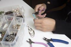 Personne faisant des bijoux avec des perles et d'autres matériaux avec des outils Images libres de droits