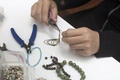 Personne faisant des bijoux avec des perles et d'autres matériaux avec des outils Photos stock