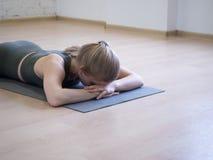 Personne fatiguée Respirez sous peu entre les exercisees Femme s'étendant sur le tapis dans la pose de détente, visage dans le pl photographie stock libre de droits