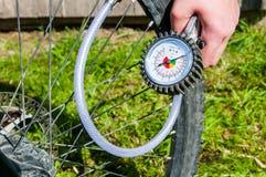 Personne gonflant le petit morceau de roue de bicyclette le compresseur d'air photographie stock