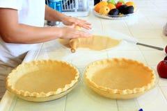 Personne malaxant une pâte à tarte pour une tarte aux pommes Image stock