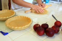 Personne malaxant une pâte à tarte pour une tarte aux pommes Photos stock