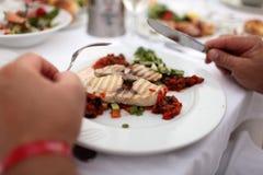 Personne mangeant les poissons grillés Photographie stock libre de droits