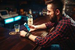 Personne masculine avec le téléphone se reposant au compteur de barre photographie stock libre de droits