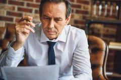Personne masculine concentrée regardant des papiers Image stock