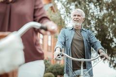 Personne masculine décontractée appréciant la promenade sur des bicyclettes image stock