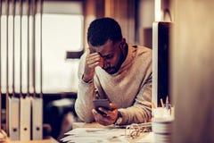 Personne masculine de brune fatiguée cintrant sa tête images stock