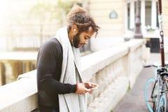 Personne masculine de mulâtre causant avec des amis par le smartphone avec l'oreille Images libres de droits