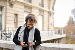Personne masculine de mulâtre causant avec des amis par le smartphone avec l'oreille Images stock