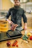 Personne masculine faisant cuire la viande dans une casserole sur la cuisine photo stock