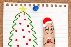 Personne mignonne de visage de doigt avec le cadeau par l'arbre de Noël Images stock