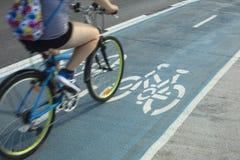 Personne montant un vélo sur la voie pour bicyclettes ou le chemin de cycle dehors Photographie stock libre de droits