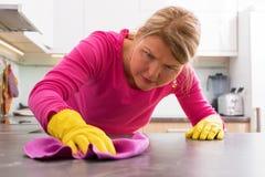 Personne nettoyant les taches dures du compteur photos stock