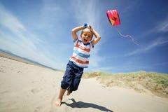 Personne pilotant un cerf-volant un jour ensoleillé avec le garçon observant en fonction Images stock