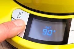 Personne plaçant la température électrique de bouilloire de thé à 90 C Photo stock