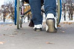 Personne poussant un fauteuil roulant en bas de la rue Images stock