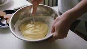 Personne préparant les oeufs de mélange d'omelette faite maison avec la corolle de main banque de vidéos