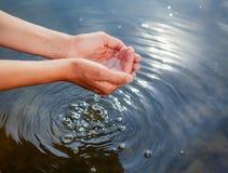 Personne prenant l'eau non filtrée crue d'un lac à la main photo stock
