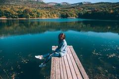 Personne s'asseyant sur le pair par le lac photo libre de droits