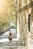 Personne sur le scooteur entraînant une réduction la rue étroite dans le village méditerranéen photo libre de droits