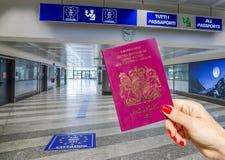 Personne tenant le passeport BRITANNIQUE dans la zone de contrôle de passeport d'aéroport Image libre de droits