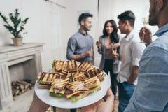 Personne tenant le plat avec les sandwichs savoureux tandis que jeunes amis de sourire buvant du champagne derrière Image stock