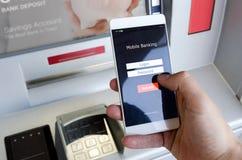 Personne tenant un téléphone avec un écran de login pour des opérations bancaires mobiles Photographie stock libre de droits