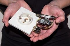 Personne tenant une prise électrique endommagée Photographie stock