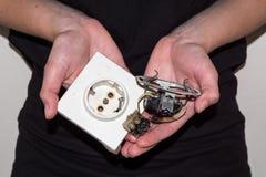 Personne tenant une prise électrique endommagée Images stock