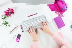 Personne travaillant au bureau blanc d'ordinateur avec le rouge et le rose Photos libres de droits